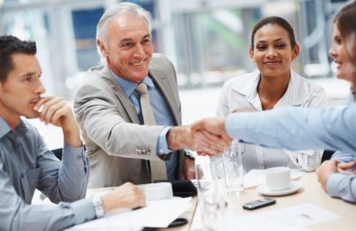 Senior business man congratulating a colleague during a meeting