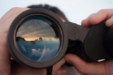 a man looking through binoculars